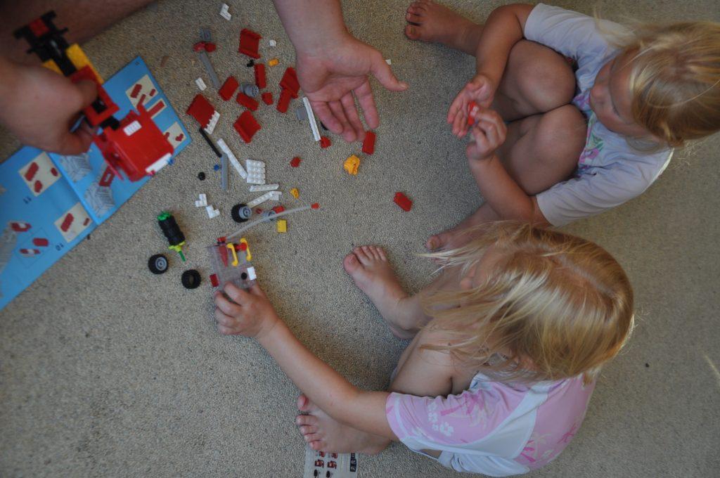 Papa helpt de dames om de brandweervrachtauto goed in elkaar te bouwen.